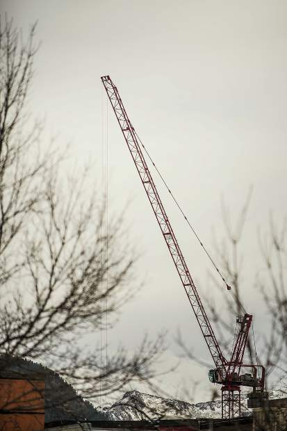 The crane above the construction at the new W Hotel sits in an overcast sky Thursday afternoon with Independence Pass in the distance.