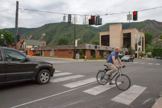 Cars wait as a bicyclist crosses at the new traffic light temporarily put in at the intersection of Eighth Street and Colorado.