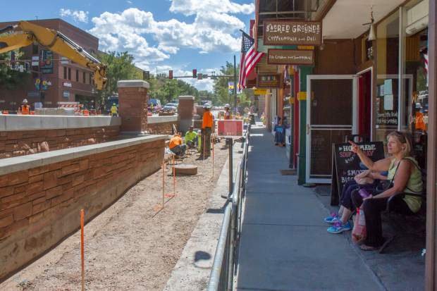 Downtown Glenwood visitors sit in front of Sacred Grounds on Wednesday for a front-row view of the work being done on the new Grand Avenue bridge.
