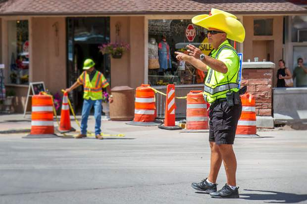 Glenwood Police Chief Terry Wilson directs traffic at Eighth Street and Grand Avenue wearing a foam cowboy hat.