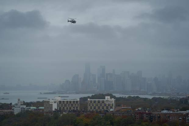 A New York City police helicopter flies near the Verrazano-Narrows Bridge during the New York City Marathon Sunday, Nov. 5, 2017, in New York. (AP Photo/Craig Ruttle)