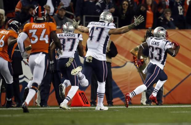 New England Patriots running back Dion Lewis (33) runs back a kick-off for a touchdown against the Denver Broncos during the first half of an NFL football game, Sunday, Nov. 12, 2017, in Denver. (AP Photo/David Zalubowski)