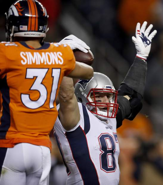 New England Patriots tight end Rob Gronkowski (87) signals a catch as Denver Broncos strong safety Justin Simmons (31) looks on during the first half of an NFL football game, Sunday, Nov. 12, 2017, in Denver. (AP Photo/David Zalubowski)