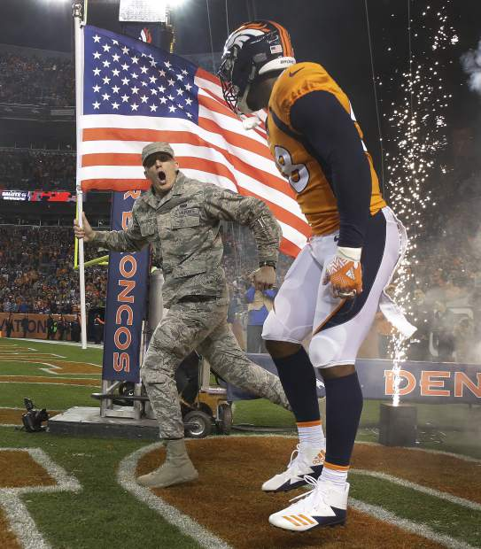 Denver Broncos outside linebacker Von Miller (58) takes the field with a U.S. Air Force airman as part of the NFL's Salute to Service prior to an NFL football game against the New England Patriots, Sunday, Nov. 12, 2017, in Denver. (AP Photo/Jack Dempsey)