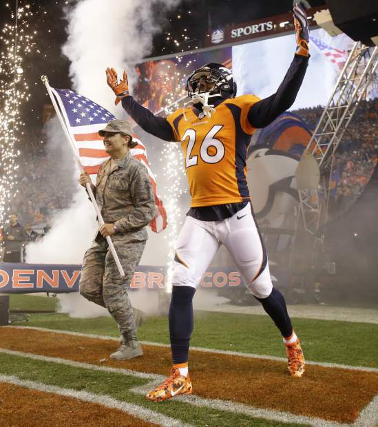 Denver Broncos free safety Darian Stewart (26) takes the field with a U.S. Air Force airman as part of the NFL's Salute to Service prior to an NFL football game against the New England Patriots, Sunday, Nov. 12, 2017, in Denver. (AP Photo/Jack Dempsey)