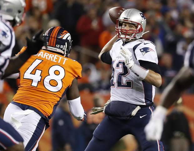 New England Patriots quarterback Tom Brady (12) throws under pressure from Denver Broncos outside linebacker Shaquil Barrett (48) during the first half of an NFL football game, Sunday, Nov. 12, 2017, in Denver. (AP Photo/Jack Dempsey)