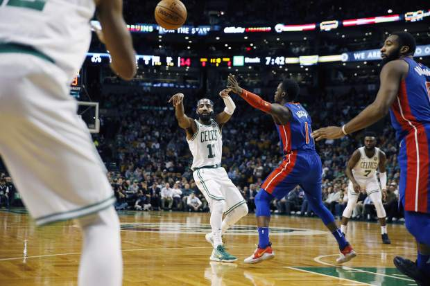 Boston Celtics' Kyrie Irving (11) passes off in front of Detroit Pistons' Reggie Jackson (1) during the first quarter of an NBA basketball game in Boston, Monday, Nov. 27, 2017. (AP Photo/Michael Dwyer)