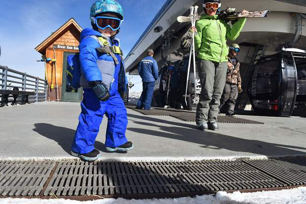 A young skier eyes the opening day snow atop Dercum Mountain after getting off at the top of the River Run Gondola during Keystone Resort's first day of the 2017-18 season on Friday Nov. 10.