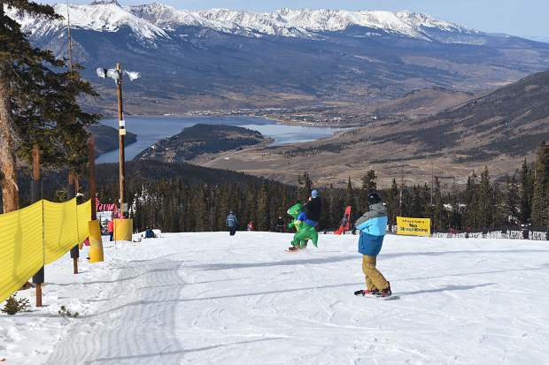 A snowboarder slips on the slope during opening day Friday, Nov. 10, at Keystone Resort.
