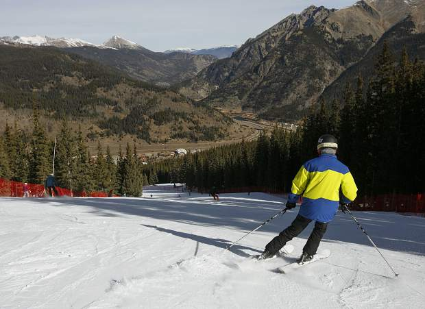 A skier rides down the mountain in front of snowless landscape during opening day Friday, Nov. 10, at Copper Mountain.