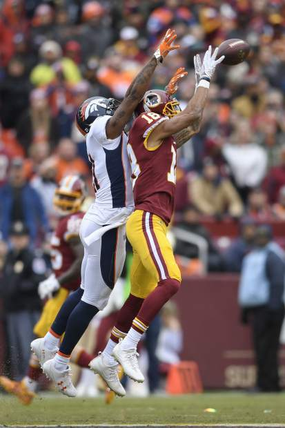 Denver Broncos cornerback Aqib Talib (21) breaks up a pass intended for Washington Redskins wide receiver Josh Doctson (18) during the first half an NFL football game in Landover, Md., Sunday, Dec 24, 2017. (AP Photo/Nick Wass)