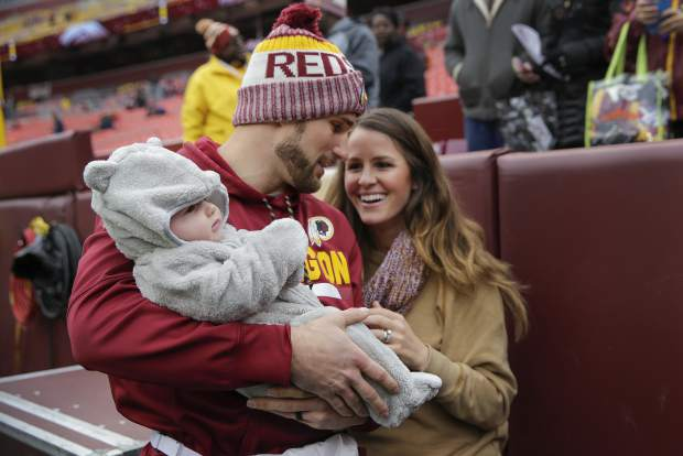 Washington Redskins quarterback Kirk Cousins (8) holds his son Cooper while talking with his wife Julie before an NFL football game against the Denver Broncos in Landover, Md., Sunday, Dec 24, 2017. (AP Photo/Mark Tenally)
