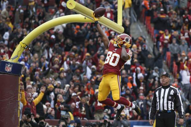 Washington Redskins wide receiver Jamison Crowder (80) celebrates his touchdown by dunking the ball over the goal posts during the first half an NFL football game against the Denver Broncos in Landover, Md., Sunday, Dec 24, 2017. (AP Photo/Alex Brandon)