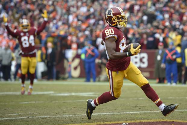 Washington Redskins wide receiver Jamison Crowder (80) carries the ball into the end zone for a touchdown as teammate Niles Paul signals the score during the first half an NFL football game against the Denver Broncos in Landover, Md., Sunday, Dec 24, 2017. (AP Photo/Nick Wass)
