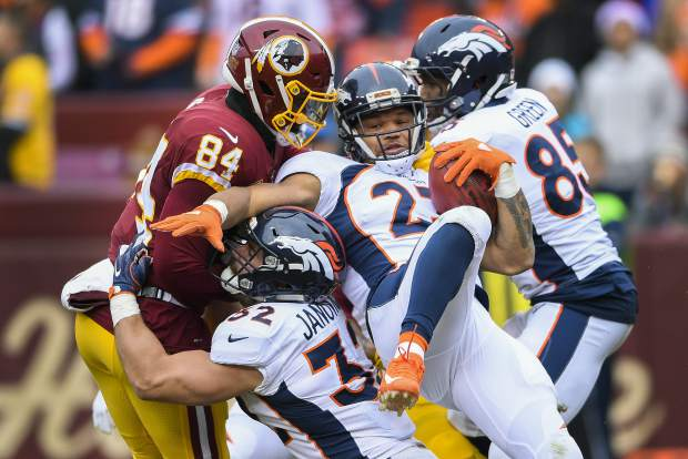 Denver Broncos running back Devontae Booker (23) is stopped by Washington Redskins tight end Niles Paul (84) during the first half an NFL football game in Landover, Md., Sunday, Dec 24, 2017. (AP Photo/Nick Wass)