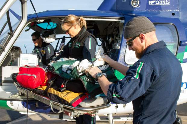 Care Flight crew members Flight Paramedic Ryan Griffin, Flight Nurse Kelly Thompson and Pilot Josh Thorne prepare the helicopter for a new shift at the Rifle Airport on Wednesday morning.