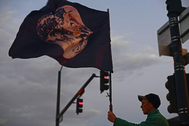 A protestor waves an earth flag outside the Alfred A. Arraj Courthouse in downtown Denver during a protest supporting a case to give the Colorado River personhood.