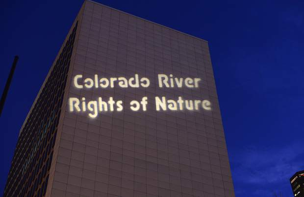 Protesters cast the words Colorado River Rights for Nature onto a building near the courthouse using a projector.