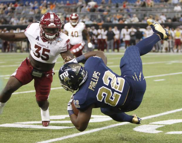 Temple linebacker William Kwenkeu (35) closes in on FIU running back Shawndarrius Phillips (22) as Phillips stumbles on the run for a short gain during the first half of the Gasparilla Bowl NCAA college football game Thursday, Dec. 21, 2017, in St. Petersburg, Fla. (Octavio Jones/The Tampa Bay Times via AP)