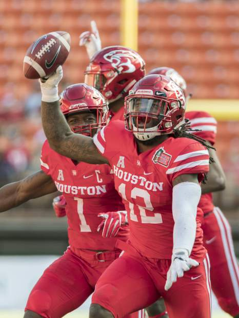 Houston linebacker D'Juan Hines (12) and his teammates celebrate the recovery of a Fresno State fumble in the first half of the Hawaii Bowl NCAA college football game, Sunday, Dec. 24, 2017, in Honolulu. (AP Photo/Eugene Tanner)