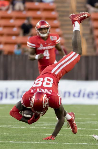 Houston wide receiver Steven Dunbar (88) is upended while running with the ball in the second half of the Hawaii Bowl NCAA college football game against Fresno State, Sunday, Dec. 24, 2017, in Honolulu. (AP Photo/Eugene Tanner)