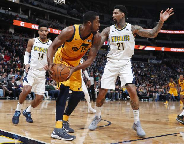 Utah Jazz forward Derrick Favors, center, pulls in a loose ball as Denver Nuggets guard Gary Harris, left, and forward Wilson Chandler defend in the second half of an NBA basketball game Tuesday, Dec. 26, 2017, in Denver. The Nuggets won 107-83. (AP Photo/David Zalubowski)