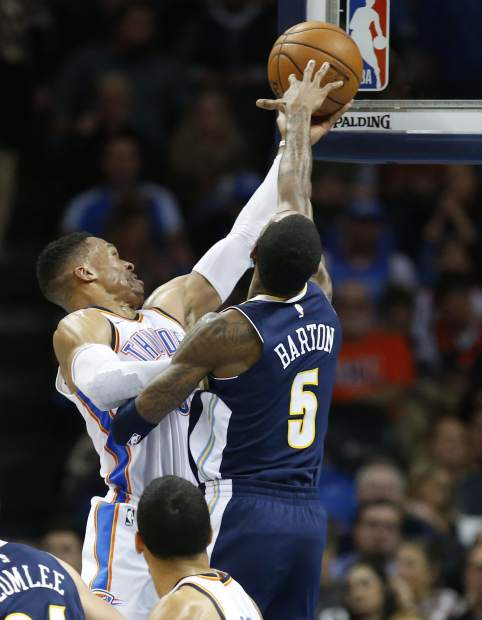 Oklahoma City Thunder guard Russell Westbrook, left, shoots as Denver Nuggets guard Will Barton (5) defends in the second quarter of an NBA basketball game in Oklahoma City, Monday, Dec. 18, 2017. (AP Photo/Sue Ogrocki)