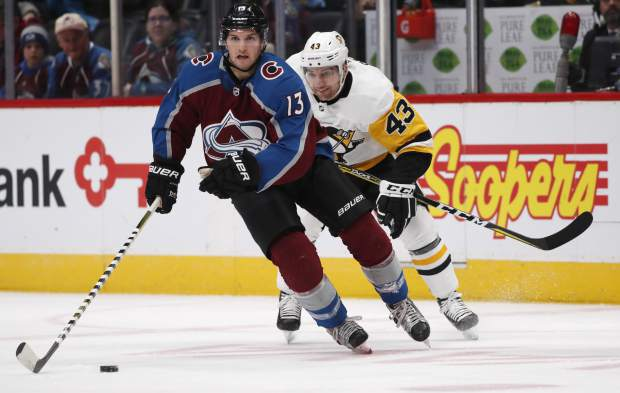 Colorado Avalanche center Alexander Kerfoot, front, moves the puck downice with Pittsburgh Penguins left wing Conor Sheary in pursuit in the first period of an NHL hockey game Monday, Dec. 18, 2017, in Denver. (AP Photo/David Zalubowski)