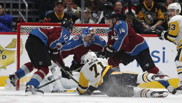 Pittsburgh Penguins center Evgeni Malkin, front, of Russia, tumbles to the ice as his shot is stopped by Colorado Avalanche goalie Semyon Varlamov, of Russia, back center, as defenseman Patrik Nemeth, left, of Sweden, and left wing Blake Comeau defend in the first period of an NHL hockey game, Monday, Dec. 18, 2017, in Denver. (AP Photo/David Zalubowski)