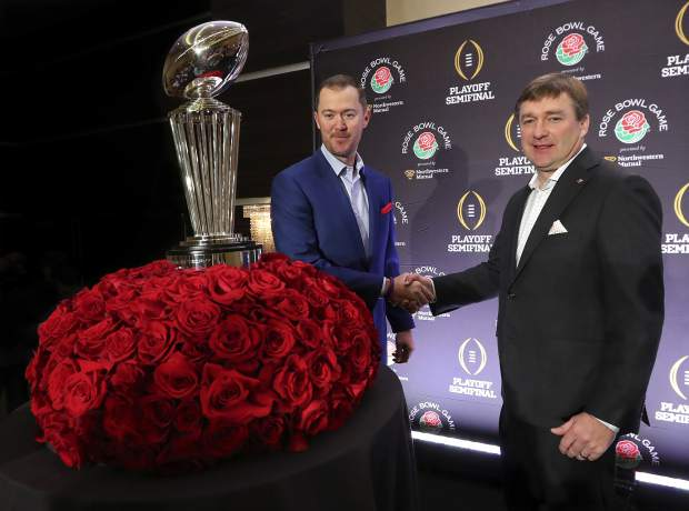 Oklahoma head coach Lincoln Riley, left, and Georgia head coach Kirby Smart shake hands next to the Rose Bowl trophy at the conclusion of a news conference with the two coaches, Sunday, Dec. 31, 2017, in Los Angeles. Oklahoma and Georgia meet at the Rose Bowl in a College Football Playoff semifinal on New Year's Day. (Curtis Compton/Atlanta Journal-Constitution via AP)