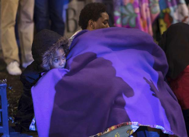 A family tries to keep warm during the Peach Drop event at Woodruff Park, Sunday, Dec. 31, 2017, in Atlanta. (Branden Camp/Atlanta Journal-Constitution via AP)