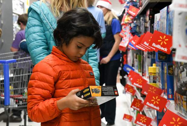 Six-year-old Maxi Pacheco picks out new lego games for himself for Christmas during the annual Shop With a Cop on Saturday afternoon.