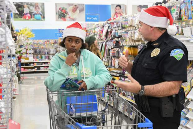 Carbondale officer Michael Zimmerman helps Arlette Gallardo pick out gifts for her mom during the annual Shop With a Cop on Saturday.