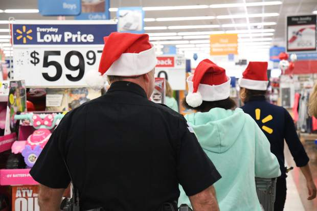 Carbondale officer Michael Zimmerman heads off with Arlette Gallardo to do some shopping at Walmart for the annual Shop With a Cop on Saturday.