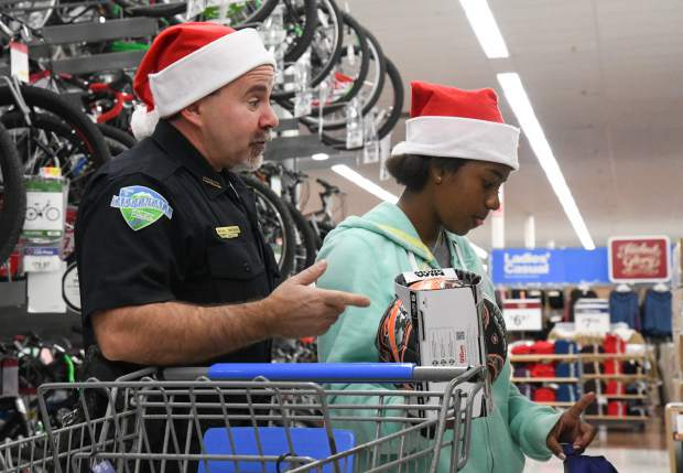 Carbondale officer Michael Zimmerman helps Arlette Gallardo pick out a new soccer ball for her brother during the annual Shop With a Cop on Saturday afternoon.