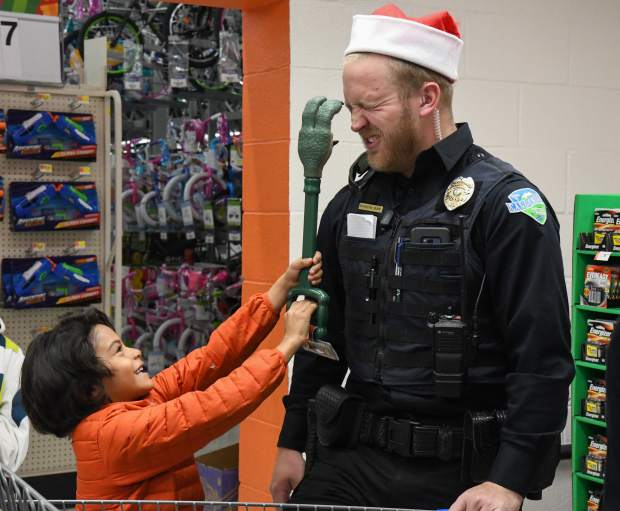 Carbondale officer Brandyn Rupp plays with 6-year-old Maxi Pacheco while they wait in line to checkout at Walmart during the annual Shop With a Cop on Saturday morning.