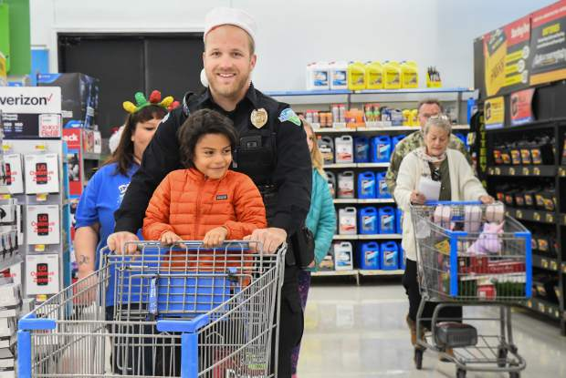 Carbondale officer Brandyn Rupp pushes 6-year-old Maxi Pacheco around on the cart while he picks out gifts for his family during the annual Shop With a Cop on Saturday afternoon. The Carbondale Police Department helped five families this year and received donations from Alpine Bank, Umbrella Roofing and Holy Cross, as well as an anonymous shopper who donated an extra $20 at the store. Each family was about to spend up to $220 on gifts. Afterwards the officers and families had lunch at McDonalds together, paid for by the Carbondale Police Department. The Glenwood Springs Police Department is also participating in the annual event.