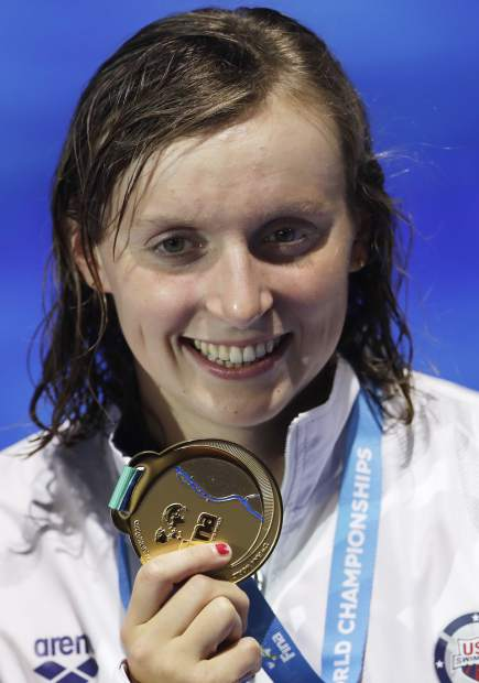 FILE - In this July 29, 2017, file photo, United States' gold medal winner Katie Ledecky shows off her medal after the women's 800-meter freestyle final during the swimming competitions of the World Aquatics Championships in Budapest, Hungary. (AP Photo/Petr David Josek, File)