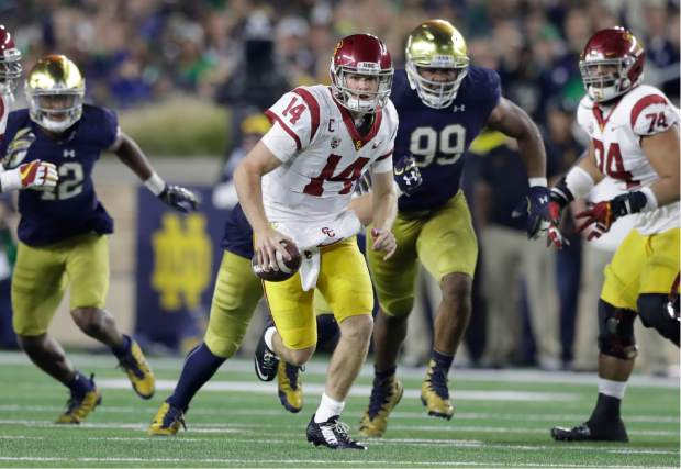FILE - In this Oct. 21, 2017, file photo, Southern California quarterback Sam Darnold scrambles during the second half of an NCAA college football game against Notre Dame in South Bend, Ind. Darnold, a third-year sophomore, hasn't said yet if he will return to eight-ranked USC for another season or if the Cotton Bowl against fifth-ranked Ohio State will be his Trojans finale. He has to decide by Jan. 15 whether to make himself eligible for the next NFL draft, which will be held in late April in the same stadium where he will play Friday night. (AP Photo/Carlos Osorio, File)