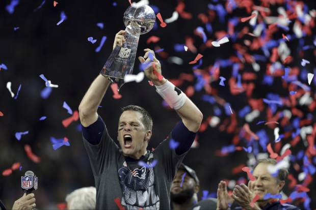 FILE - In this Feb. 5, 2017, file photo, New England Patriots' Tom Brady raises the Vince Lombardi Trophy after defeating the Atlanta Falcons in overtime at the NFL Super Bowl 51 football game in Houston. In a season that included his suspension for
