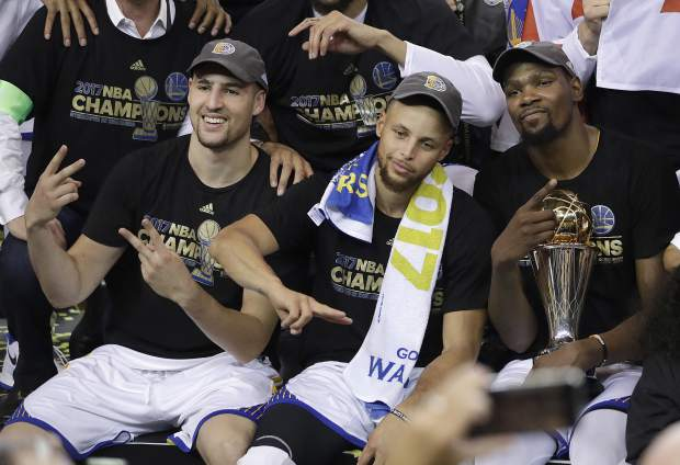 FILE - In this June 12, 2017, file photo, Golden State Warriors guard Klay Thompson, from left, guard Stephen Curry and forward Kevin Durant celebrate after Game 5 of basketball's NBA Finals against the Cleveland Cavaliers in Oakland, Calif. Durant leading the Golden State Warriors to the NBA championship over the defending champion Cleveland Cavaliers was one of the biggest sports stories in 2017. (AP Photo/Marcio Jose Sanchez, File)
