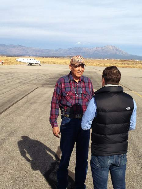 Mark Maryboy, left, a Navajo leader, is interviewed by a reporter from the BBC Sunday at the Blanding, Utah, airport. The Abajo Mountains are in the background of this view looking north.