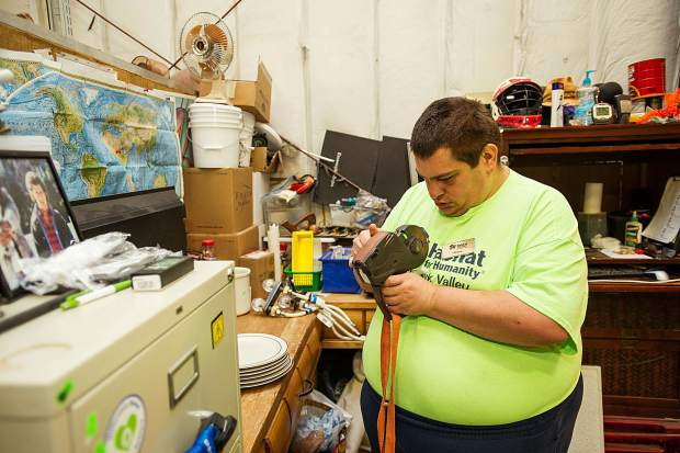 Habitat for Humanity employee Brian Wilson prepares the pricing machine while working at the downvalley ReStore on Wednesday. Wilson received a plaque acknowledging him as