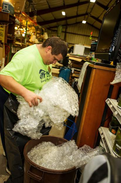Habitat for Humanity Roaring Fork employee Brian Wilson removes bubble wrap from donations received at the ReStore on Wednesday.