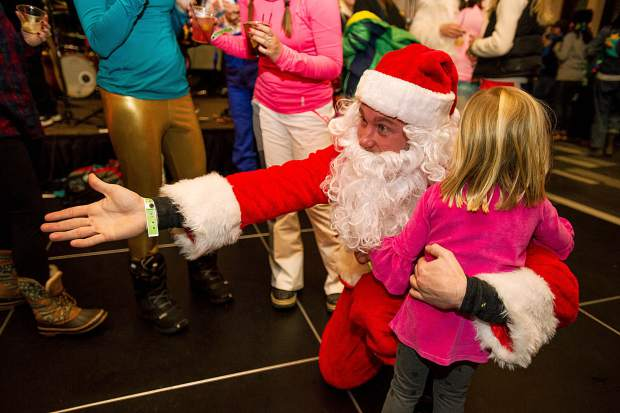 Emily Bassion, 4, hugs Santa at the retro party at the Elk Camp Lodge in Snowmass Friday night for the 50th anniversary celebrations.