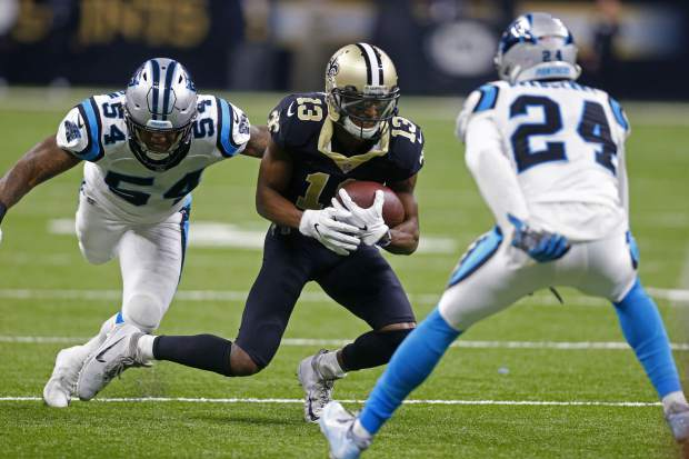 New Orleans Saints wide receiver Michael Thomas (13) carries on a pass reception between Carolina Panthers outside linebacker Shaq Green-Thompson (54) and cornerback James Bradberry (24) in the first half of an NFL football game in New Orleans, Sunday, Jan. 7, 2018. (AP Photo/Butch Dill)