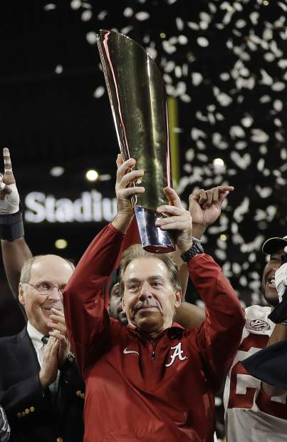 Alabama head coach Nick Saban holds up the championship trophy after overtime of the NCAA college football playoff championship game against Georgia, Monday, Jan. 8, 2018, in Atlanta. Alabama won 26-23. (AP Photo/David J. Phillip)