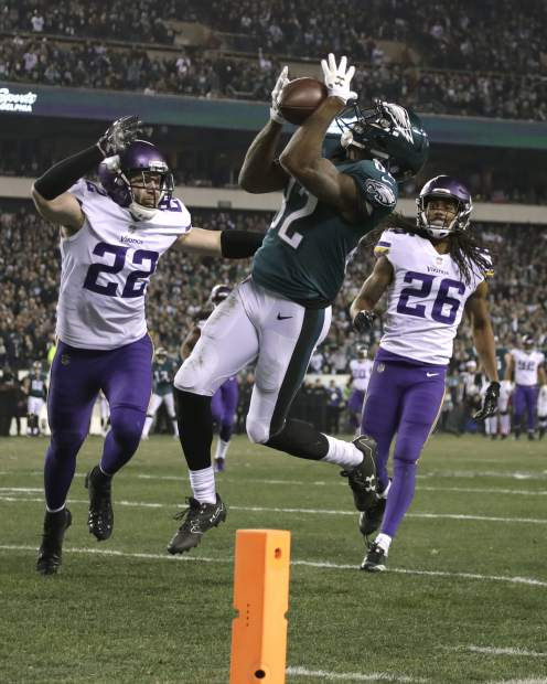 Philadelphia Eagles' Torrey Smith catches a touchdown pass in front of Minnesota Vikings' Trae Waynes (26) and Harrison Smith (22) during the second half of the NFL football NFC championship game Sunday, in Philadelphia.