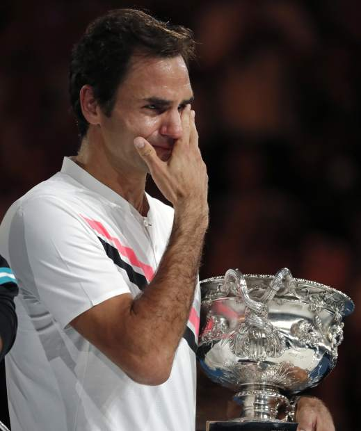 Switzerland's Roger Federer wipes tears away from his eyes as he holds his trophy after defeating Croatia's Marin Cilic during the men's singles final at the Australian Open tennis championships in Melbourne, Australia, Sunday, Jan. 28, 2018. (AP Photo/Vincent Thian)