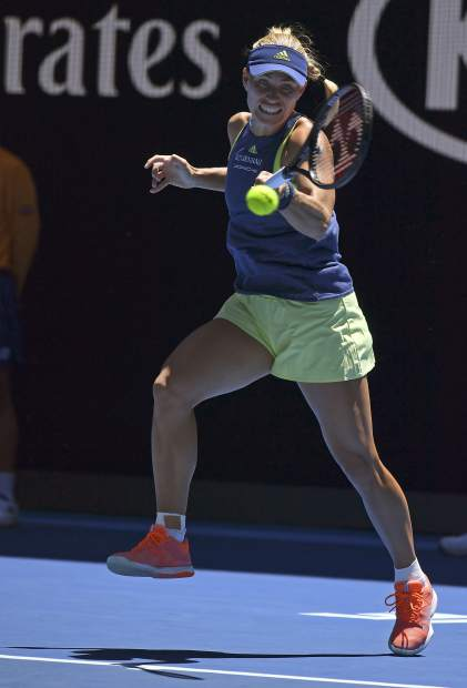 Germany's Angelique Kerber makes a backhand return to compatriot Anna-Lena Friedsam during their first round match at the Australian Open tennis championships in Melbourne, Australia, Tuesday, Jan. 16, 2018. (AP Photo/Andy Brownbill)